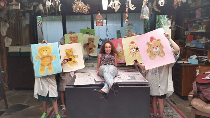 ArtCool for Kids Terry Taylor in workshop with children holding up images of teddy bears